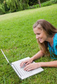 Smiling young woman lying in a park while working on her laptop — Stock Photo