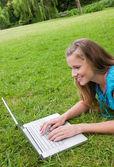 Улыбаясь молодая женщина, лежа в парке во время работы на своем ноутбуке — Стоковое фото