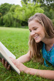 Young girl reading a book in a parkland while laughing — Stock Photo