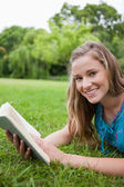 Smiling teenage girl holding a book in a parkland while looking — Stock Photo