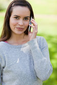 Peaceful young woman using her mobile phone while standing in a — Stock Photo