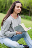 Thoughtful young woman holding a book while sitting on the grass — Stock Photo
