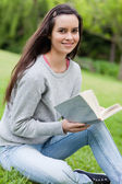 Young smiling woman holding her book while looking at the camera — Stock Photo