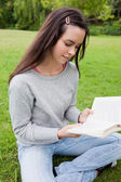 Young calm girl reading a book while sitting on the grass — Stock Photo