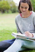 Young smiling girl writing on her notebook while sitting in a pa — Stockfoto