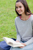 Smiling young woman looking away while holding a book — Stock Photo
