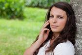 молодая женщина серьезные, позвонив со своего мобильного телефона во время сидения — Стоковое фото