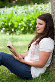 Young thoughtful girl leaning against a tree while reading a boo — Stock Photo
