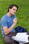 年轻有思想的人坐在草地上时按住他的笔 — 图库照片