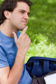 Young man placing his finger on his chin while sitting in a park — Stock Photo