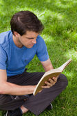 Young serious man sitting cross-legged while reading a book — Stock Photo