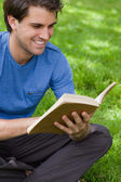 Young smiling man reading a book while siting on the grass — Stock Photo
