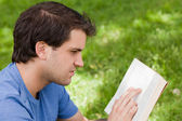 Young serious man reading a book while sitting in a park — Stock fotografie