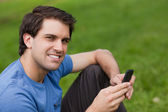 Glad ung man tittar på kameran när du skickar en text — Stockfoto
