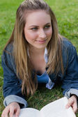 Young smiling girl looking towards the side while lying on the g — Stock Photo