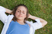 Young relaxed girl napping on the grass while placing her hands — Stock Photo