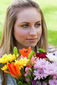 Bir demet çiçek looki süre tutarak rahat sarışın kız — Stok fotoğraf