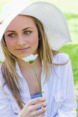 Young peaceful girl holding a white flower in a park — Stock Photo