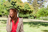 Young woman enthusiastically laughing while on the phone in an o — Stock Photo