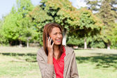 Young woman talking on the phone while looking toward the side i — 图库照片