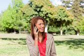 молодая женщина разговаривает по телефону, глядя на стороне — Стоковое фото
