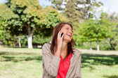 Woman laughing joyfully on a phone while standing in a sunny gra — Stock Photo