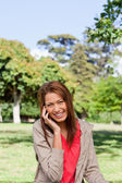 Young woman smiling while looking into the camera in a bright gr — Stock Photo