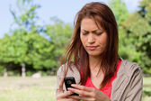 Young woman with a concerned expression reading a text message — Stock Photo