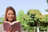 Young woman happily reading a book in a sunny park — Stock Photo