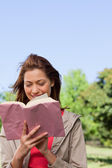 Woman happily reading a book with the wind blowing through her h — Stock Photo