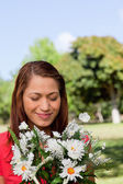 Young woman examining a bunch of flowers while standing in a par — ストック写真