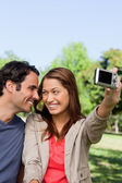 Young woman and her friend look at each other while she takes a — Stock Photo