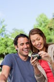 Two friends smiling happily as the look at the photo collection — Stock Photo