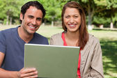 Two smiling friends looking ahead as they hold a tablet — Stock Photo
