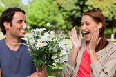 Kadın gülüyor heyecanla onun tarafından çiçeklerle sunulur — Stok fotoğraf