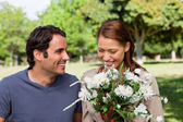 Woman happily looking into a bunch flowers as she is being watch — Stock Photo