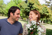 Man watches his friend laughing while holding a bunch of flowers — Stock Photo