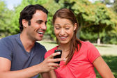 Man laughing as he shows something on his phone to his friend — Stock Photo