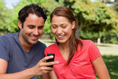 Two friends smiling as they are looking at something on a mobile — Stock Photo