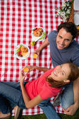 Elevated view of two smiling friends as they lie on a blanket wi — Stock Photo