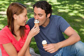 Woman feeding her friend ice cream — Stock Photo