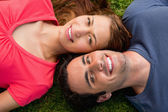 Two friends smiling while lying head to shoulder — Stock Photo