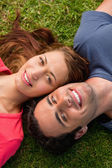 Close-up of two friends smiling while lying head to shoulder — Stock Photo