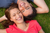 Two friends smiling while lying head to shoulder with an arm beh — Stock Photo