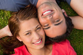 Close-up of two friends looking upwards while lying head to shou — Stockfoto