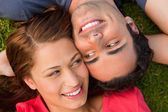 Close-up two friends looking at each other while lying head to s — Stock Photo