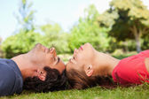Two friends with their eyes closed while lying head to head — Stock Photo
