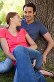 Woman looking at her friend while they sit together in the shade — Stock Photo