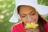 Woman wearing a white hat while smelling a flower with her eyes — Stock Photo