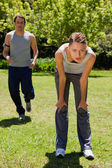 Woman bending over while a man is jogging in the background — Stock Photo